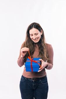 Веселая молодая женщина открывает подарочную коробку на белом фоне