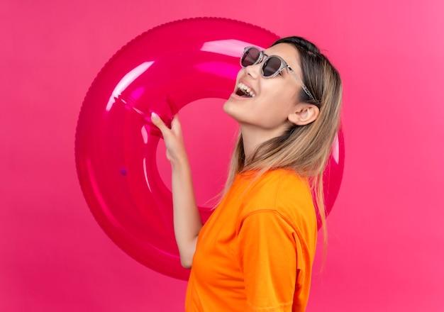 Una giovane donna allegra in una maglietta arancione che indossa occhiali da sole guardando il lato mentre tiene l'anello gonfiabile rosa su una parete rosa