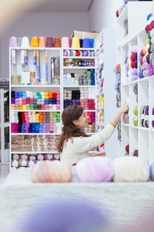 Cheerful young woman organizing shelves at a retail business