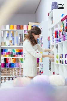 Cheerful young woman organizing wools at a retail business