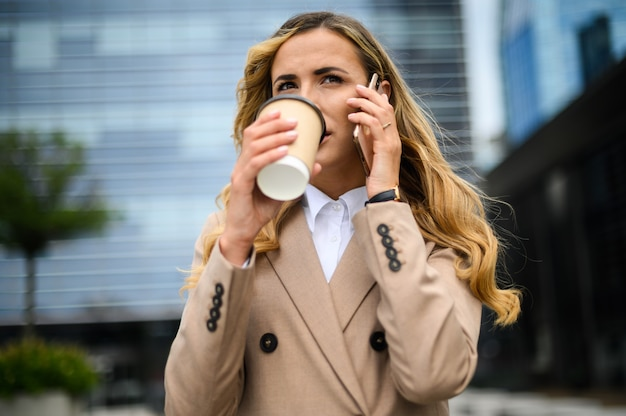 Cheerful young woman on the phone outdoor in a modern urban setting while drinking coffee