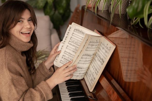 陽気な若い女性ピアニストがノートをめくってピアノに座っています