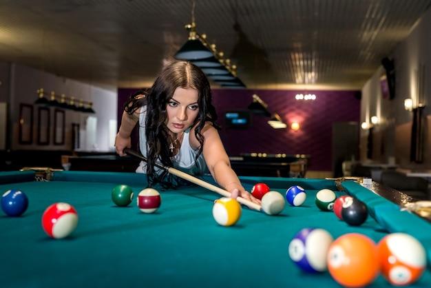 Веселая молодая женщина играет в американский бильярд.