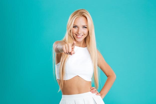 青い背景で隔離のカメラに指を指している陽気な若い女性