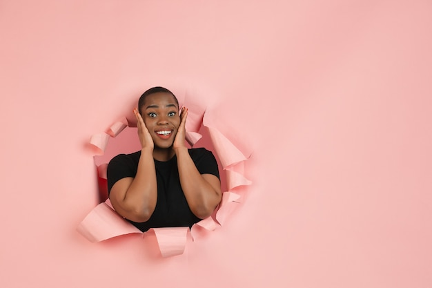 Cheerful young woman poses astonished in torn coral paper hole