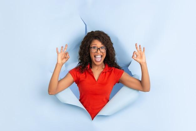 쾌활한 젊은 여성이 찢어진 파란 종이 구멍에서 감정적이고 표현력이 풍부한 포즈를 취합니다.