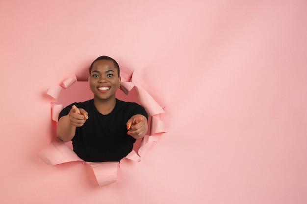 陽気な若い女性は、感情的で表現力豊かな引き裂かれた珊瑚紙の穴の壁でポーズをとる