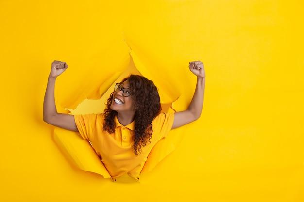 引き裂かれた黄色の紙穴背景、感情的で表現力豊かな陽気な若い女性のポーズ