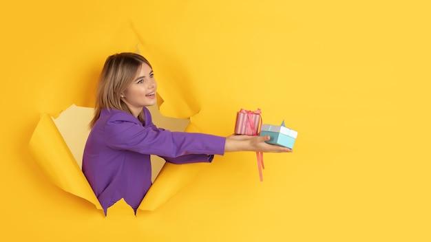 陽気な若い女性は、感情的で表現力豊かな、引き裂かれた黄色い紙の穴でポーズをとる