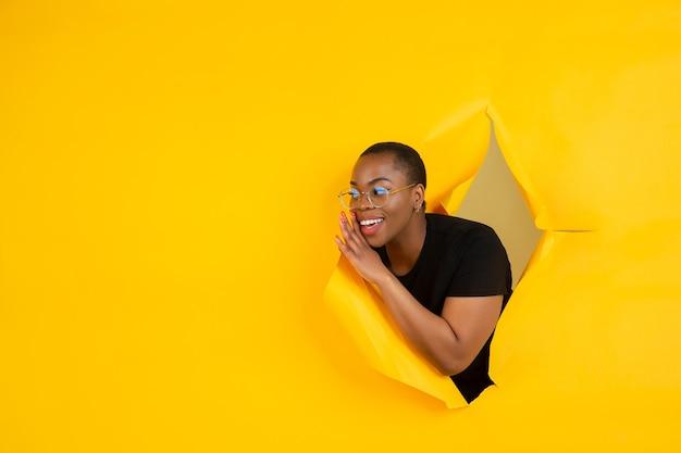 感情的で表情豊かな破れた黄色い紙の穴の壁で陽気な若い女性のポーズ