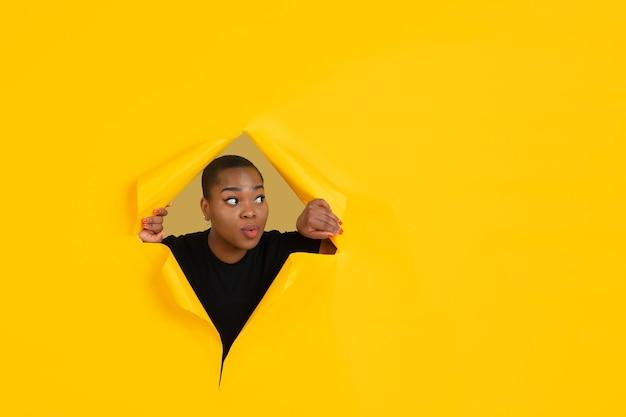 陽気な若い女性は、感情的で表現力豊かな引き裂かれた黄色い紙の穴の壁でポーズをとる
