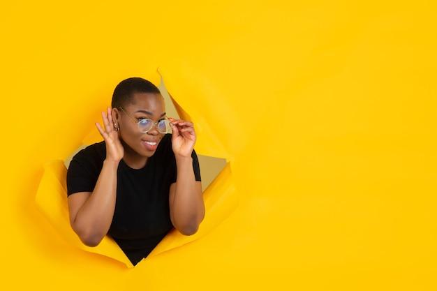 찢어진 노란 종이 구멍에 쾌활 한 젊은 여자 포즈