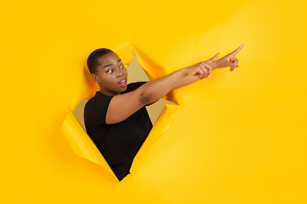引き裂かれた黄色い紙の穴で陽気な若い女性のポーズ
