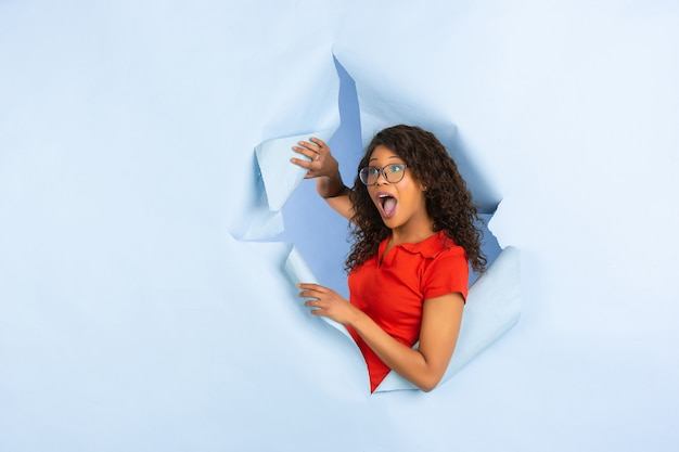 Cheerful young woman poses in torn blue paper hole background, emotional and expressive