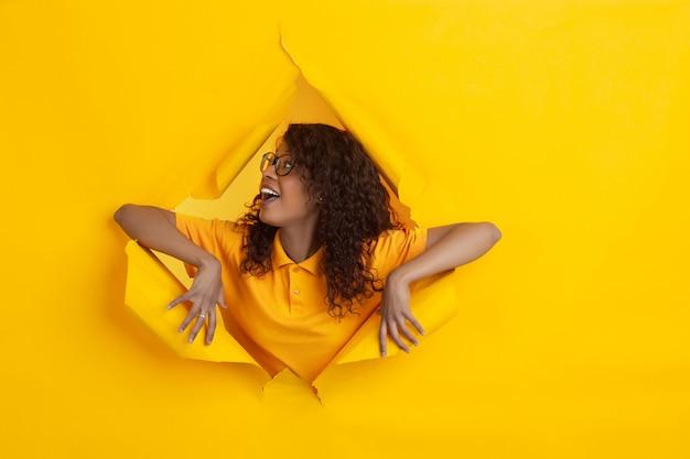 La giovane donna allegra posa nel fondo lacerato del foro della carta gialla, emozionale ed espressivo