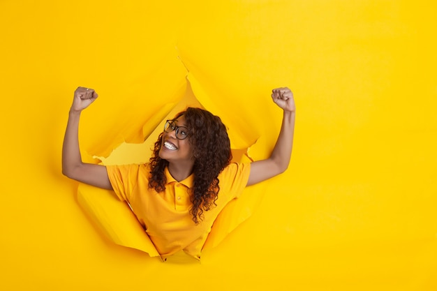 Cheerful young woman poses in torn yellow paper hole background, emotional and expressive