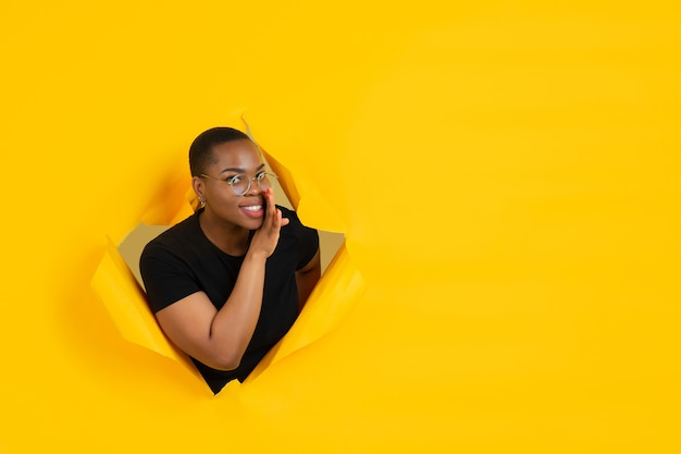 Una giovane donna allegra posa in un muro strappato di carta gialla emotiva ed espressiva