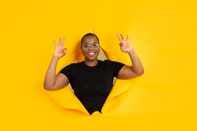 La giovane donna allegra posa nel buco di carta gialla strappata