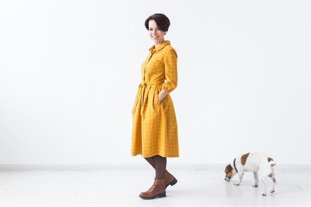 Веселая молодая женщина позирует в желтом платье