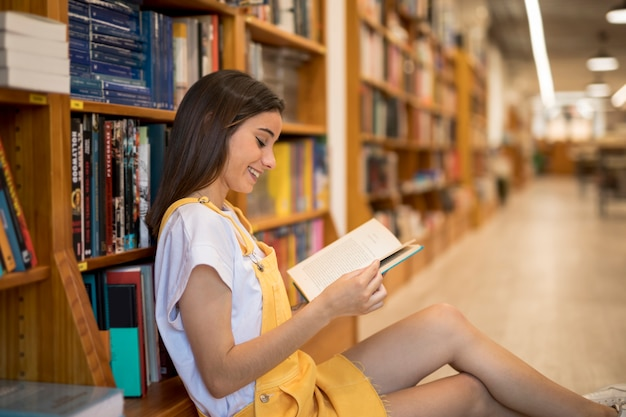 Cheerful young woman reading book in library