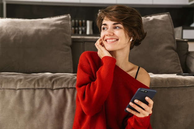 Cheerful young woman relaxing at home, listening to music with wireless earphones