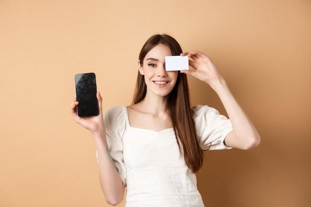 プラスチックのクレジットカードと空の携帯電話の画面を表示し、カメラに満足して笑って、ベージュの上に立っている陽気な若い女性。
