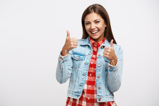 Cheerful young woman showing thumbs up