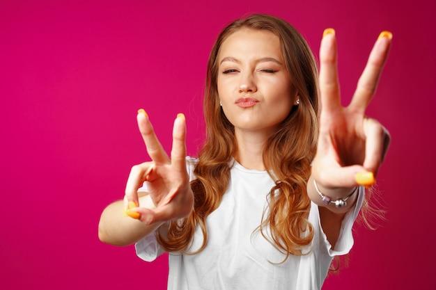 勝利の手サインを示す陽気な若い女性