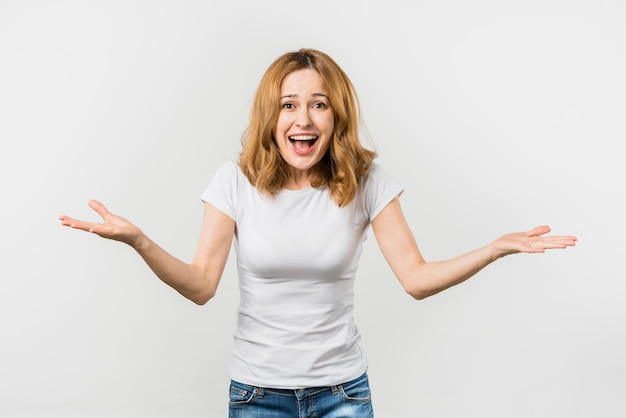 Cheerful young woman shrugging against white background