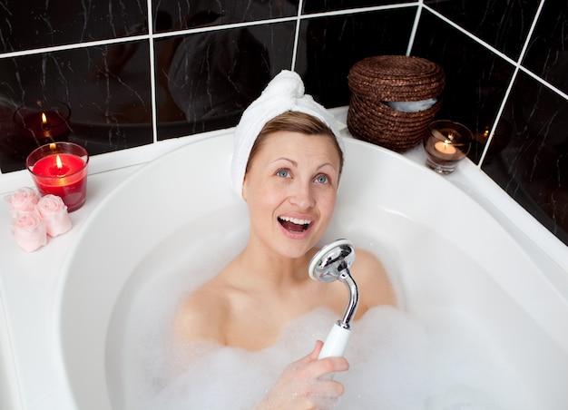 Веселая молодая женщина, поющая в пузырьковой ванне