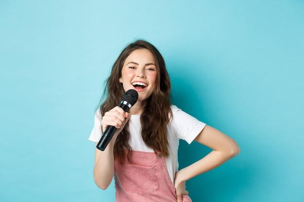 Веселая молодая женщина поет караоке, держа микрофон и улыбаясь, весело, стоя на синем фоне.