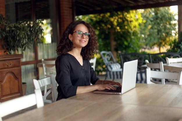 ラップトップで入力してテーブルに座っている陽気な若い女性