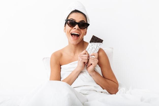 毛布に包まれたシャワーの後、サングラスをかけて、チョコレートバーを食べてベッドに座っている陽気な若い女性