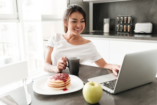 Cheerful young woman sitting at the kitchen using laptop