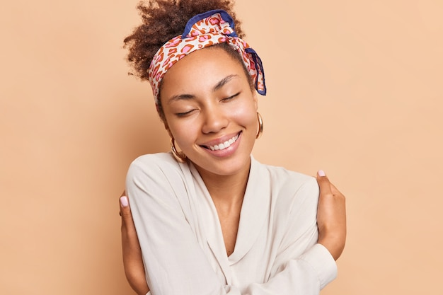 Веселая молодая женщина улыбается, нежно трогает плечи, обнимает себя, держит глаза закрытыми, носит повязку на голову, белую рубашку, изолированную над бежевой стеной студии