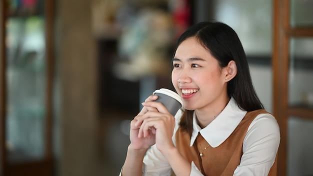 Веселая молодая женщина улыбается и держит чашку кофе, сидя в кафе