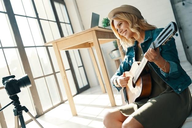 쾌활한 젊은 여자가 미소하고 디지털 카메라 앞에서 기타를 연주하는 동안 기타를 연주