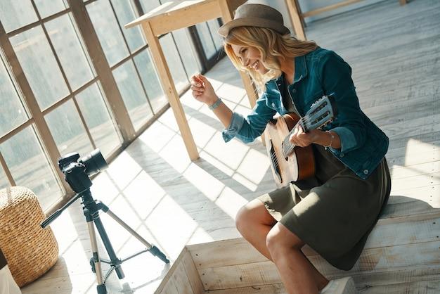 쾌활한 젊은 여자가 미소하고 디지털 카메라 앞에서 기타를 연주하는 동안 기타를 연주 프리미엄 사진