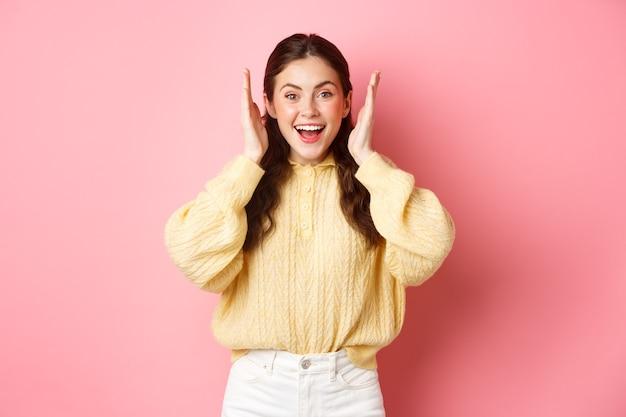Веселая молодая женщина улыбается, выглядит взволнованной, открывает уши после громкого взрыва или фейерверка, празднует что-то, стоя у розовой яркой стены