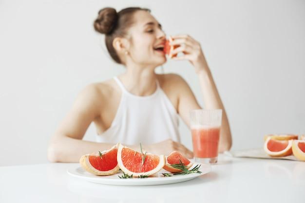 白い壁にグレープフルーツの部分を食べるテーブルに座って笑っている陽気な若い女性。健康食品のコンセプトです。