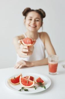 白い壁にグレープフルーツのストレッチ部分をテーブルに座って笑っている陽気な若い女性。健康食品のコンセプトです。