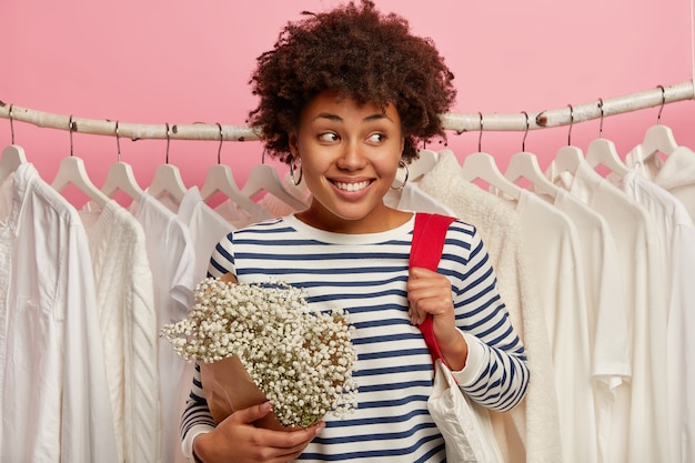 Cheerful young woman spends free time in shopping mall, looks aside with broad smile, carries fabric bag, stands over white clothes hanging in row, isolated on pink background.
