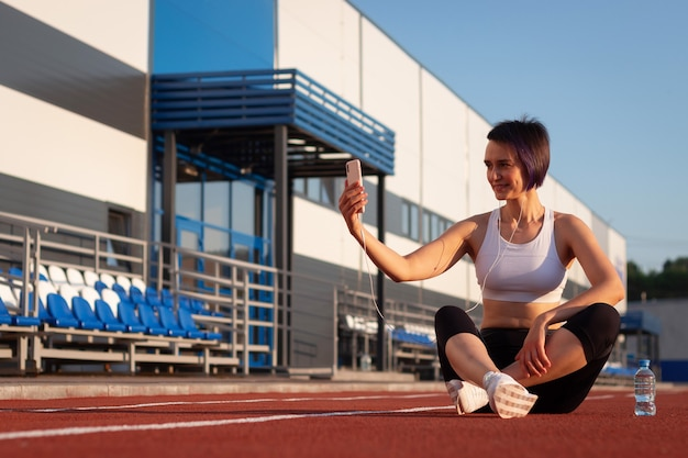 A cheerful young woman in sportswear relaxing after a workout or run, sitting on a stadium track, taking selfies, listening to music on headphones on her smartphone, taking a break during a workout