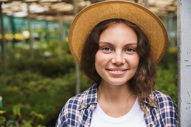 온실에 서있는 쾌활 한 젊은 여자