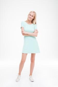 白い壁に立っている陽気な若い女性。正面を見てください。腕を組んでポーズをとる