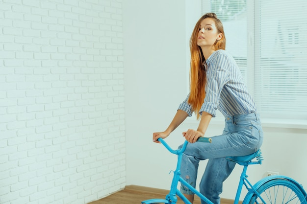 Cheerful young woman standing near bicycle