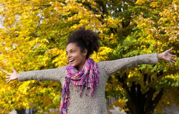 Веселая молодая женщина, стоя на открытом воздухе с вытянутыми руками