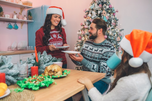 쾌활 한 젊은 여성이 tabel 웃 고 서있다. 그녀는 손에 접시를 보유하고 있습니다. 여자는 그들을 남편에게 준다. 그는 그녀를보고 웃었다. 딸도 테이블에 앉아 있습니다. 그들은 축제 저녁을 먹습니다.