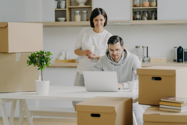 Cheerful young woman stands behind her husband who works on laptop computer, pose in modern kitchen of their new apartment, surrounded with cardboard boxes, think about modern design