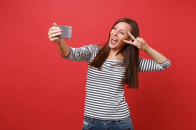 Cheerful young woman in striped clothes doing taking selfie shot on mobile phone showing victory sign isolated on bright red background. people sincere emotions, lifestyle concept. mock up copy space.